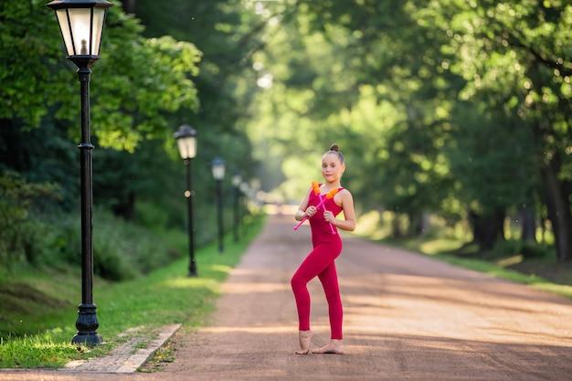 Dziewczyna gimnastyczka w jaskrawoczerwonym kombinezonie robi ćwiczenia z pałkami w parku w ciepły słoneczny wieczór