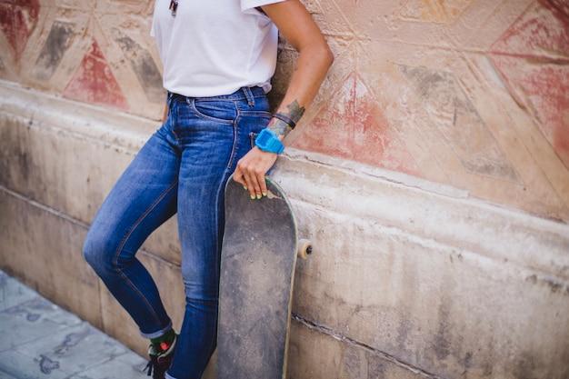 Dziewczyna gospodarstwa skateboard le? enia na betonowej? cianie