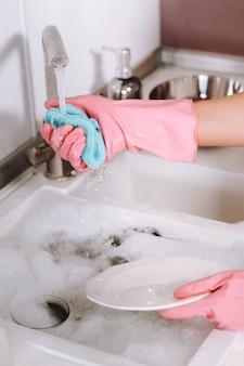 Dziewczyna gospodyni w różowych rękawiczkach zmywa ręcznie naczynia w zlewie z detergentem. dziewczyna sprząta w domu i zmywa naczynia w rękawiczkach w domu.