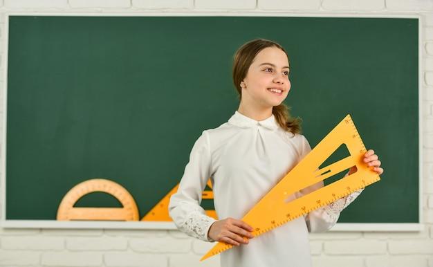 Dziewczyna gotowa do nauki. uczennica w szkole. uczyć się matematyki z trójkątem. dziecko w szkole podstawowej. badanie ucznia za pomocą narzędzia geometrii. powrót do szkoły. dzieciak z wyposażeniem. mierzenie i liczenie.