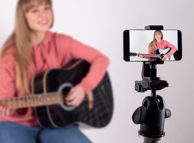 Dziewczyna gra na gitarze, aby udostępnić ją w sieciach społecznościowych