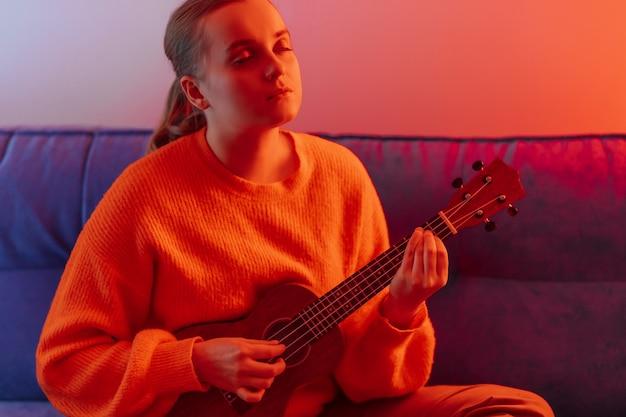 Dziewczyna gra na ukulele w wielobarwnym świetle