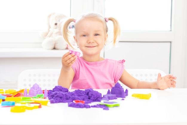 Dziewczyna gra piasek kinetyczny w kwarantannie. blond piękna dziewczyna uśmiecha się i gra z fioletowym piaskiem na białym stole.