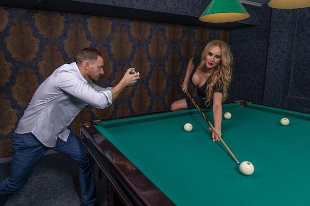 Dziewczyna gra w bilard i celuje kijem w piłkę, a mężczyzna chce ją sfotografować starym aparatem