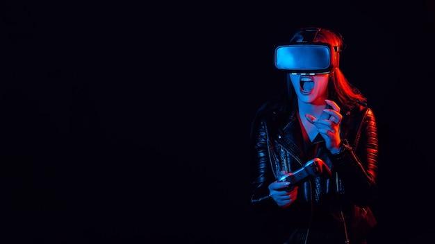 Dziewczyna gra w nowoczesne gry komputerowe w okularach wirtualnej rzeczywistości. emocjonalny gracz z joystickiem w dłoniach zanurza się w świecie rozszerzonej rzeczywistości z pomocą nowoczesnych innowacji