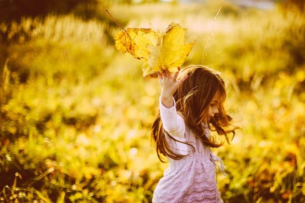 Dziewczyna gra z opadłych liści w godzinach wieczornych
