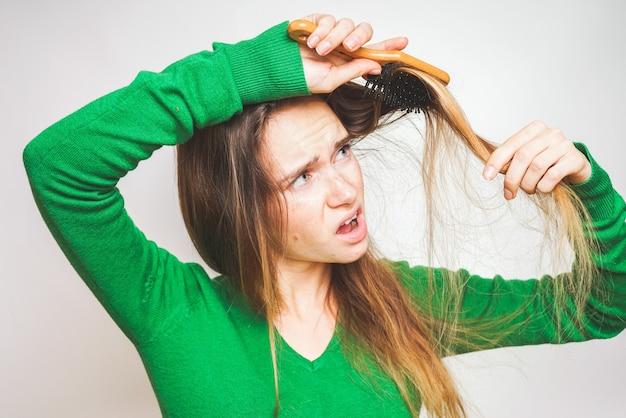 Dziewczyna grzebie włosy na białym tle, wypadanie włosów, łysienie. utracone włosy