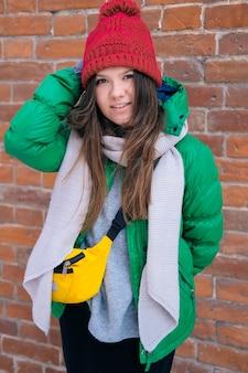 Dziewczyna hipster w jasne ubrania, śmiejąc się i uśmiechając przed murem. młoda szczęśliwa kobieta w czerwonej czapce, zielonej kurtce, szarym szaliku, żółtej małej torebce. kobieca moda.