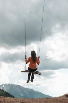 Dziewczyna huśta się na huśtawce nad górami, uczucie lotu i wolności.