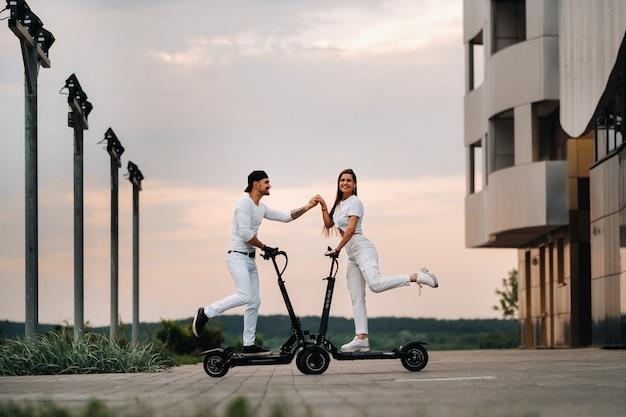 Dziewczyna i chłopak spacerują po mieście na skuterach elektrycznych, zakochana para na skuterach