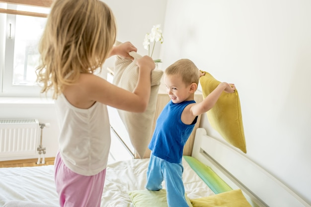 Dziewczyna i chłopak, uśmiechając się i walcząc na poduszki na łóżku