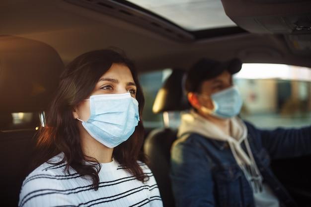 Dziewczyna i chłopiec w maskach medycznych jadący samochodem podczas kwarantanny koronawirusa