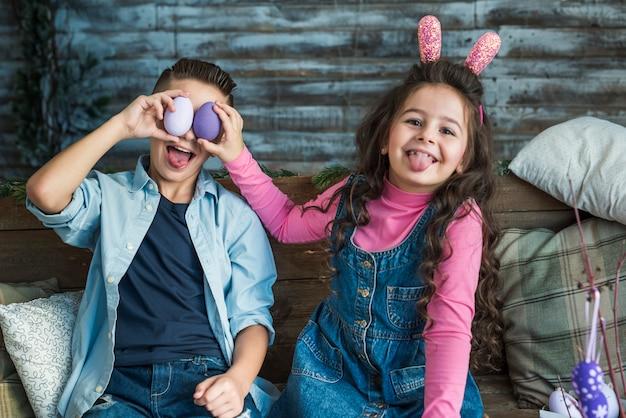 Dziewczyna i chłopiec z wielkanocnymi jajkami robi twarzom