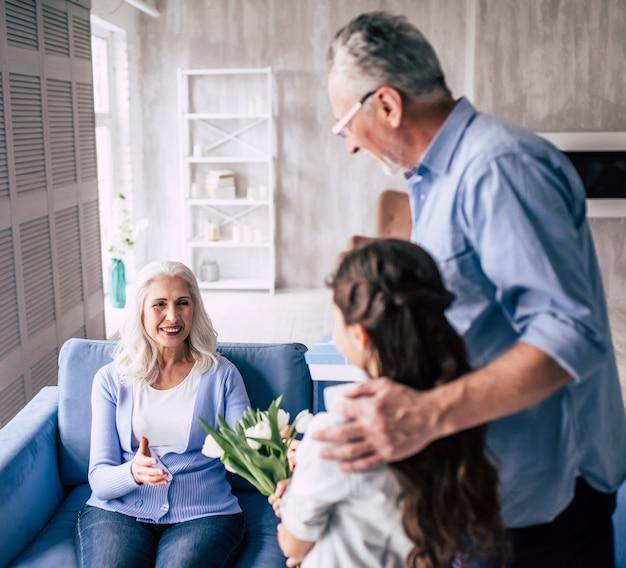 Dziewczyna i dziadek dają kwiaty babci