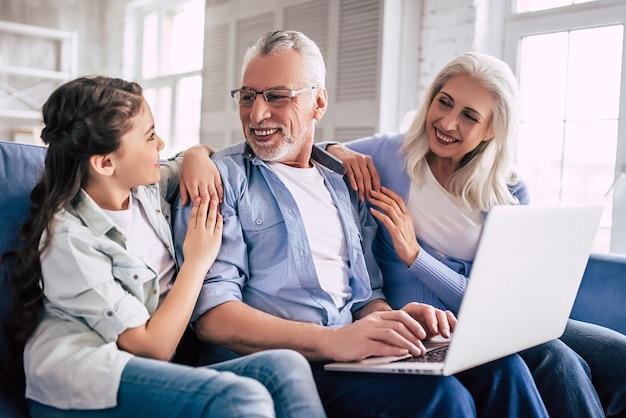 Dziewczyna i dziadkowie siedzą z laptopem