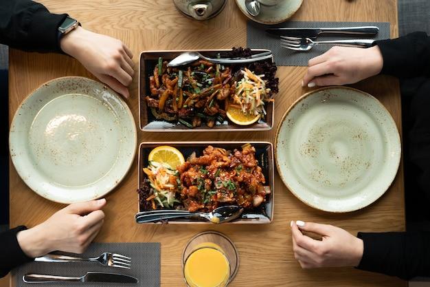 Dziewczyna i facet przy stole jedzą obiad lub kolację w azjatyckiej restauracji. lunch w restauracji. dwa.