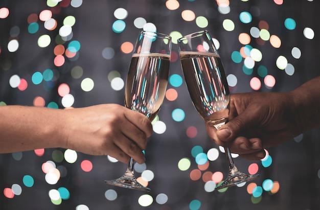 Dziewczyna i facet są parowani kieliszkami szampana na pięknych świątecznych światłach bokeh