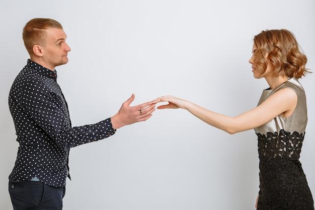 Dziewczyna i facet stoją przed sobą i wyciągają do siebie ręce.