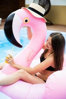 Dziewczyna i flamingo floatie z kapeluszem
