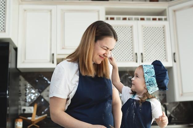 Dziewczyna i jej mama w dopasowanych fartuchach i czapkach bawią się podczas wyrabiania ciasta w kuchni