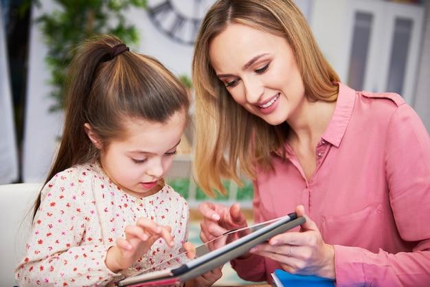 Dziewczyna i jej młoda mama używają tabletu w domu