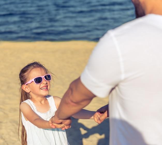 Dziewczyna i jej młody tata w słońc szkłach trzymają ręki