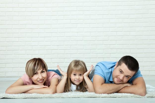 Dziewczyna i jej rodzice, leżąc na dywanie w salonie.