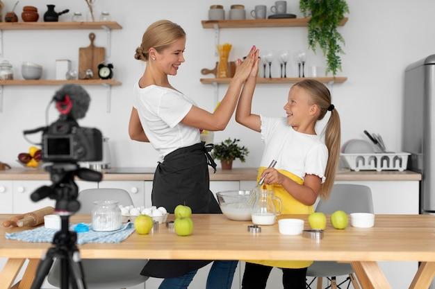 Dziewczyna i kobieta przygotowujące jedzenie średni strzał
