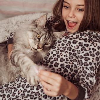 Dziewczyna i kot bawią się w łóżku