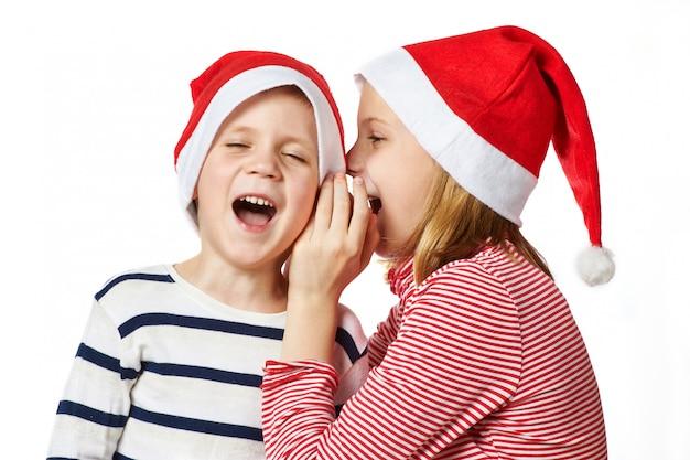 Dziewczyna i mały chłopiec w santa claus hat