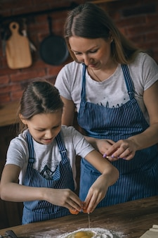 Dziewczyna i matka pęka jajka na mąkę