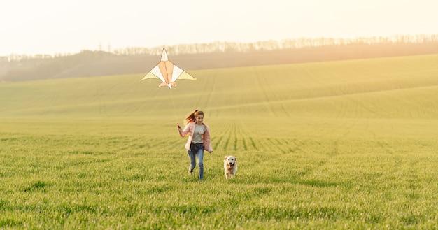 Dziewczyna i pies bawi się z latawcem