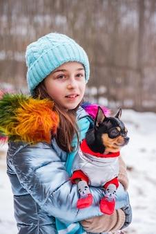 Dziewczyna i pies w ubraniach, zima. nastolatka w niebieskiej kurtce, kapeluszu i szaliku. dziewczyna i chihuahua.