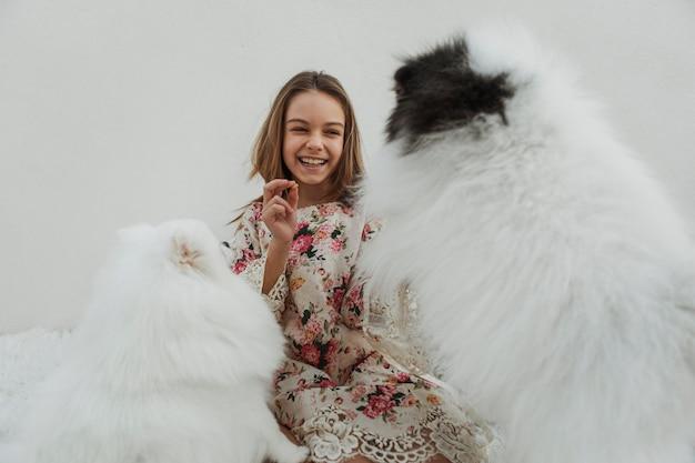Dziewczyna i słodkie białe szczenięta bawiące się w aport