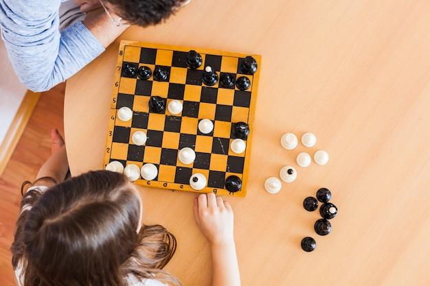 Dziewczyna i tata grają w domu, szachy, puzzle dla rozwoju mózgu, inteligencji umysłowej