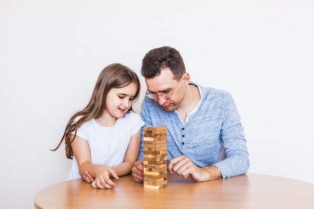 Dziewczyna i tata grają w grę w domu, kosztują wieżę bloków, kostki, jengę, puzzle dla rozwoju mózgu, inteligencję umysłową