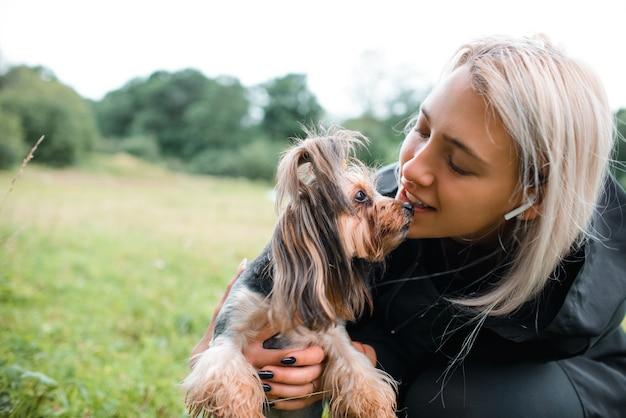 Dziewczyna i yorkshire terrier na spacer po parku. pani trzymająca zwierzaka w ramionach, selektywna ostrość