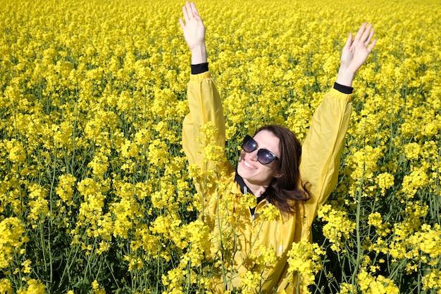 Dziewczyna i żółte kwiaty rzepaku. roślina oleista. wyjedź poza miasto. letnia słoneczna pogoda.