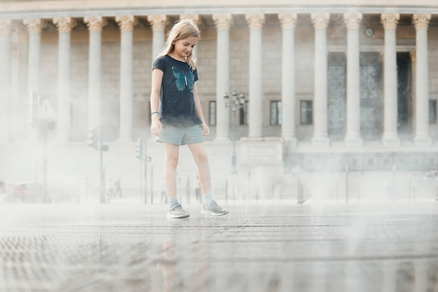 Dziewczyna idąc przez plac z biczami wodnymi na tle starego budynku z kolumnami