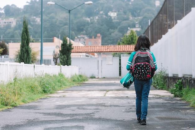Dziewczyna idąca do wejścia do szkoły z powrotem do szkoły
