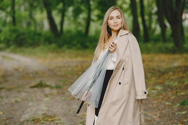 Dziewczyna idzie. kobieta w brązowym płaszczu. blondynka z parasolem.