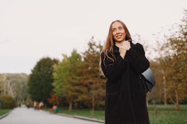 Dziewczyna idzie. kobieta w czarnym płaszczu. pani na zewnątrz.