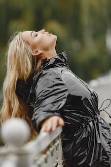 Dziewczyna idzie. kobieta w czarnym płaszczu.