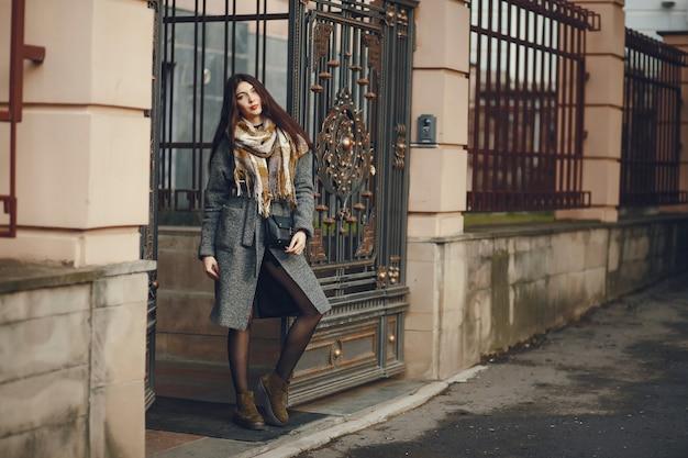 Dziewczyna idzie. kobieta w płaszczu. brunetka z szalikiem.