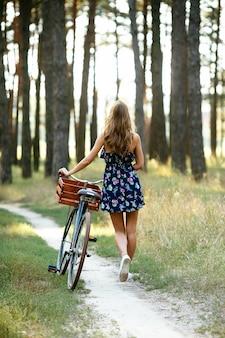 Dziewczyna idzie na ścieżce rowerowej w lesie