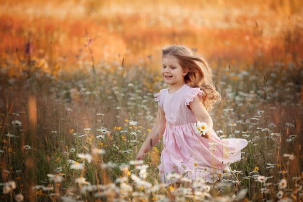 Dziewczyna idzie po polu ze stokrotkami