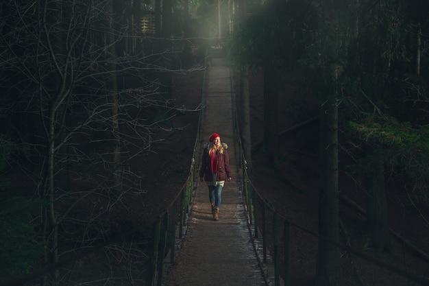 Dziewczyna idzie po wiszącym moście nad górską rzeką. mroczny, mistyczny las.