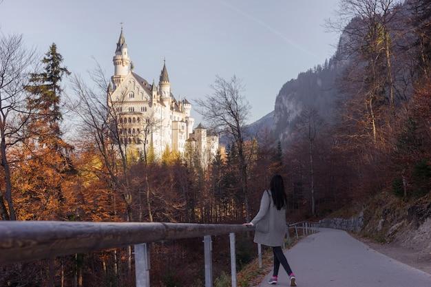 Dziewczyna idzie ścieżką w lesie jesienią do bardzo pięknego zamku neuschwanstein w niemczech.