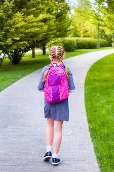 Dziewczyna idzie się uczyć. widok z tyłu w parku. w mundurku i tornistrze. szkoła podstawowa, pierwsza klasa