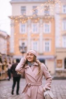 Dziewczyna idzie ulicą jarmarku bożonarodzeniowego, udekorowana na boże narodzenie